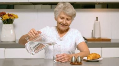 Retired woman pouring glass of water for breakfast — Stock Video