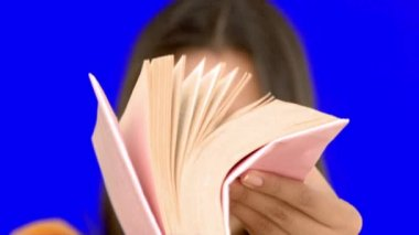 Woman flipping through a pink book on blue screen — Stock Video