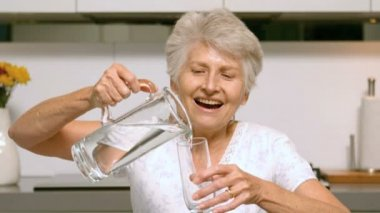Happy woman pouring glass of water — Stock Video