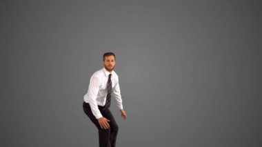 Businessman leaping up and grabbing legs on grey background — Stock Video