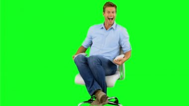 Smiling man turning on swivel chair on green screen — Stock Video