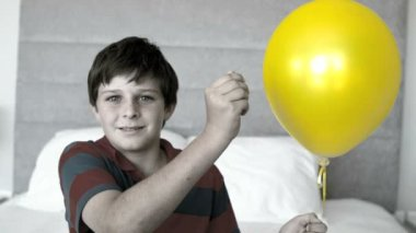 Boy piercing his balloon in the bedroom in selective color — Stock Video