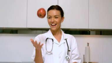 Home nurse throwing and catching apple and smiling in kitchen — Stock Video