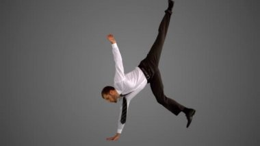 Businessman doing one hand handstand on grey background — Stock Video