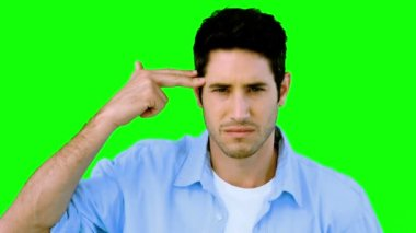 Man låtsas skjuta sig själv med handen på grön skärm — Stockvideo