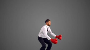 Businessman in boxing gloves jumping and punching on grey background — Stock Video