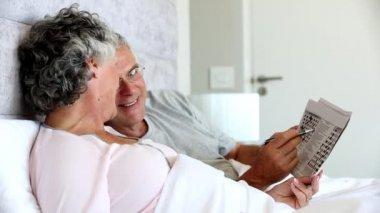 Ouder paar oplossen kruiswoordraadsel in het bed — Stockvideo