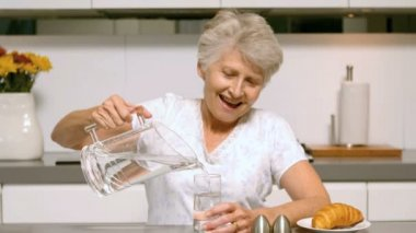 Elderly woman pouring a glass of water for breakfast — Stock Video