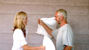 Mature couple pillow fighting at home — Stock Video