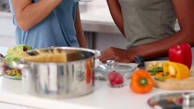 Друзья, расслабляющий с красным вином во время приготовления еды — Стоковое видео