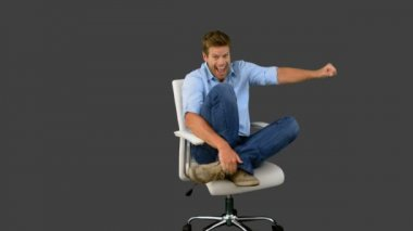 Smiling man cheering and turning on swivel chair on grey screen — Stock Video