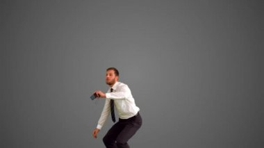 Businessman leaping and taking self portrait on grey background — Stock Video