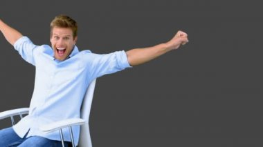Man on swivel chair raising arms to show his success on grey screen — Stock Video
