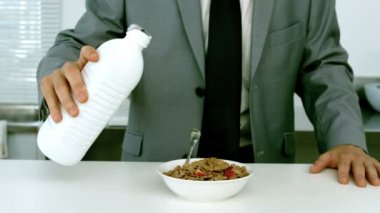 Well dressed businessman pouring milk into his cereals — Stock Video