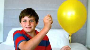 Boy piercing his balloon in the bedroom — Stock Video