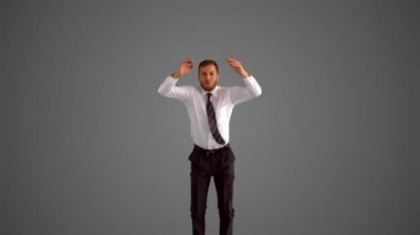 Businessman jumping and doing the splits on grey background — Stock Video