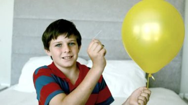 Boy piercing his yellow balloon and getting a fright — Stock Video