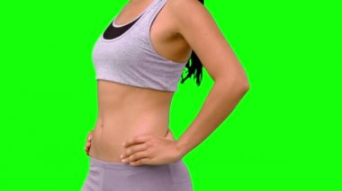 Athletic woman turning to camera against green screen — Stock Video