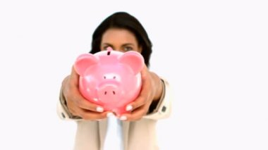 Businesswoman showing piggy bank to the camera — Stock Video