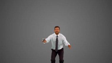 Businessman holding alarm clock jumping on grey background — Stock Video