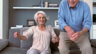 Retired couple flopping down on the couch — Stock Video