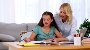 Mother helping her daughter with homework and smiling at desk in living room