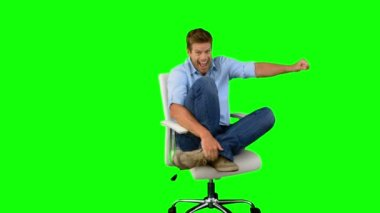 Smiling man cheering and turning on swivel chair on green screen — Stock Video