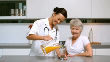 Home nurse pouring orange juice for patient in kitchen — Stock Video