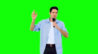 Man singing into microphone and dancing on green screen — Stock Video