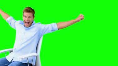 Man sitting on swivel chair with raised arms to show his success on green screen — Stock Video