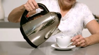 Woman pouring boiling water from kettle into cup — Stock Video