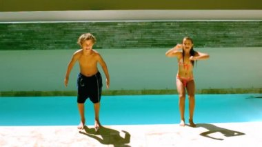 Siblings jumping together in the swimming pool — Stock Video