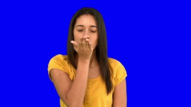 Woman blowing a kiss on blue screen — Stock Video