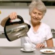 Stock Video: Elderly woman pouring boiling water from kettle into cup in kitchen