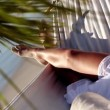 Woman relaxing in a hammock under a palm tree — Stockvideo
