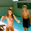 Young girl dancing while brother jumping in the swimming pool — 图库视频影像