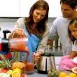 Woman with family pouring fruit cocktail from a blender — Vídeo de stock