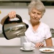 Retired woman pouring boiling water from kettle into cup in kitchen — Stock Video #25691257