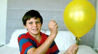 Niño recibiendo un buen susto y piercing su globo amarillo — Vídeo de stock