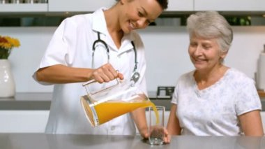 Home help pouring orange juice for patient in kitchen — Stock Video