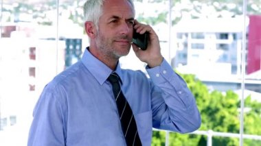 Businessman answering his phone and looking impressed — Stock Video