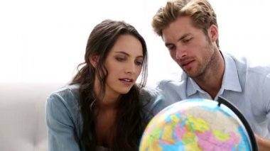 Couple looking at globe and picking travel destination — Stock Video