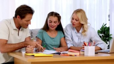 Parents proud of their daughters homework at desk in living room