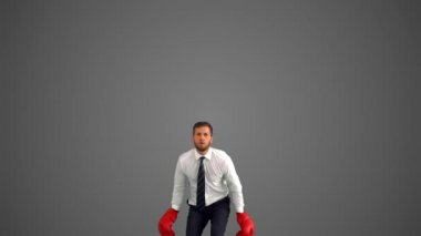 Businessman in boxing gloves leaping and punching his fists on grey background — Stock Video