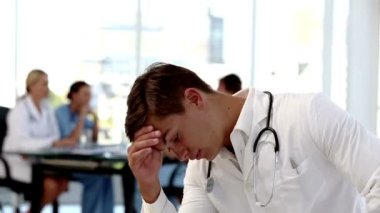Young worried doctor holding his head — Stock Video