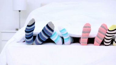 Familys feet in stripey socks kicking under the covers — Stock Video