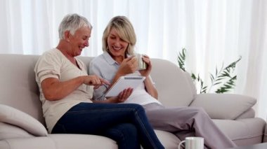 Mature women using tablet pc on the couch — Stock Video