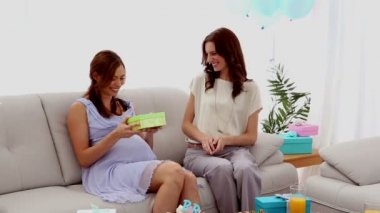Expectant mother opening a present from friend — Stock Video