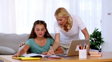 Mother helping her daughter with homework — Stock Video #25691283