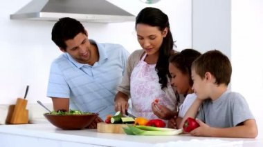 Mother showing children how to chop vegetables — Stock Video